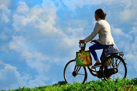 女性と自転車と空